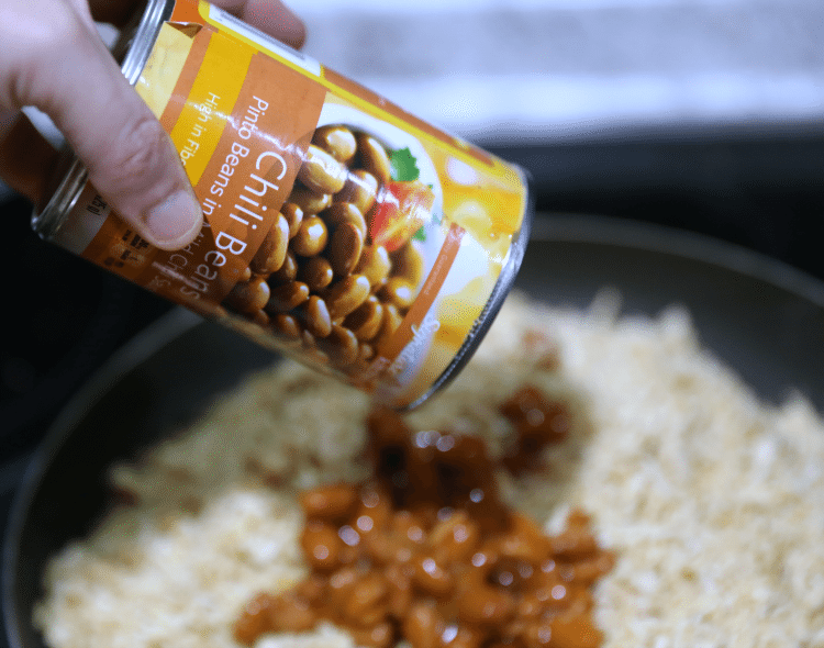 pouring chili beans into chicken
