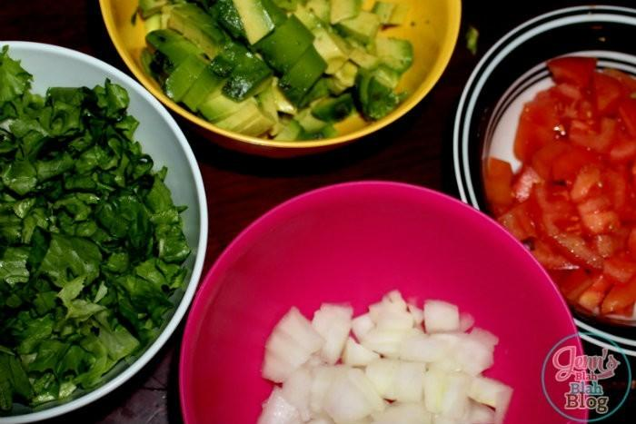 lettuce, onions, tomatos, and avacado on a table