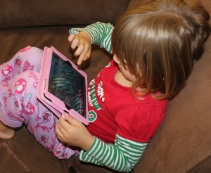little girl playing game on ipad mini