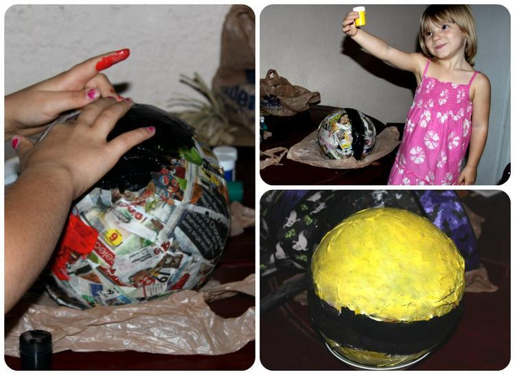 two girls painting their paper mache bugs with black and yellow paint