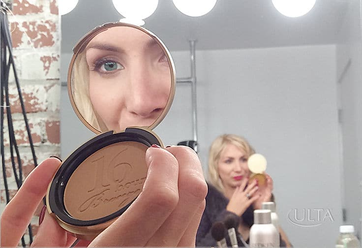 women using ULTA beauty makeup looking in the mirror smiling.