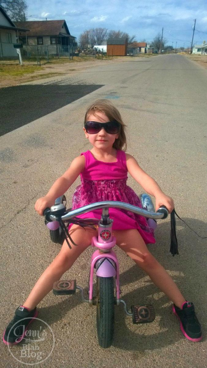 black and white picture of toddler on bike wearing sunglasses looking cool