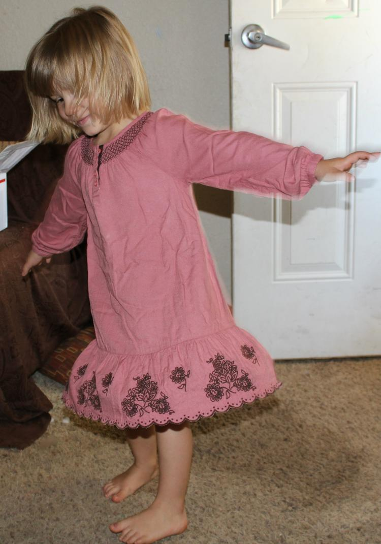 girl showing off her cute pink dress that her mom rentedf fpr jer