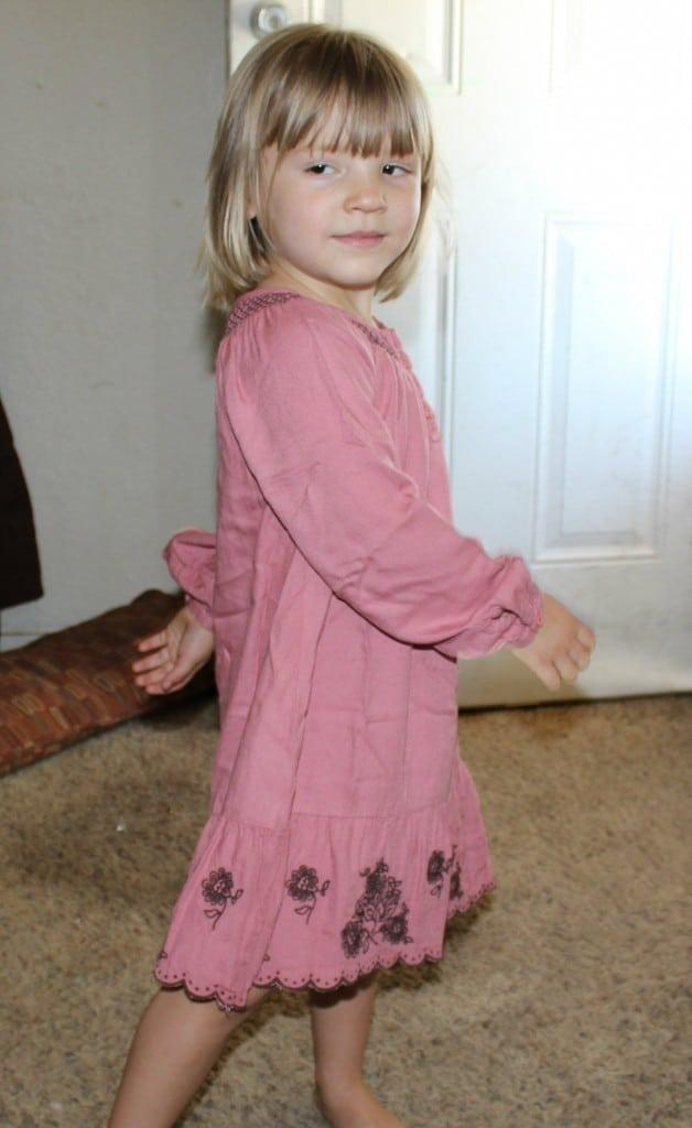 toddler spinning around in a pink dress that her mom rented